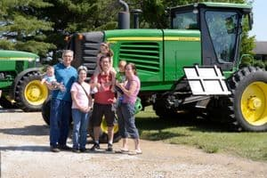 Family smiling in front of tractor